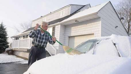 Herb Hohne, cleans snow off his vehicle in