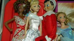Elf hangs out with Barbie dolls.