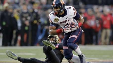 Navy wide receiver Jamir Tillman rushes past Army