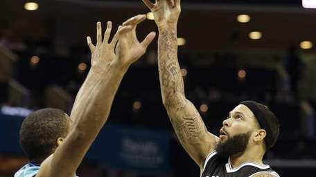 Brooklyn Nets' Deron Williams, right, shoots over Charlotte