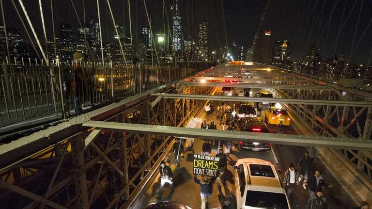 Demonstrators march over the inbound lane of the