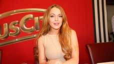 """Lindsay Lohan attends a news conference during """"Weisses"""
