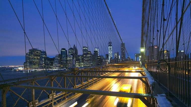 Traffic crosses the Brooklyn Bridge at dawn toward