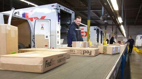 FedEx workers handle packages at the company facility
