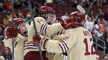 Boston College's Johnny Gaudreau, center, jumps into the