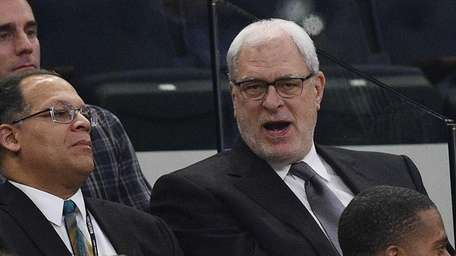 Phil Jackson, right, attends a game between the