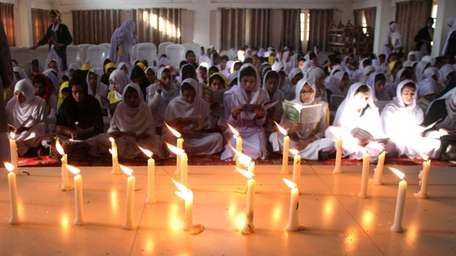 Pakistani schoolchildren pray for victims who were killed