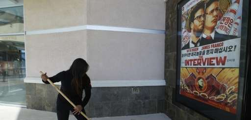 A movie theater worker sweeps rain water under