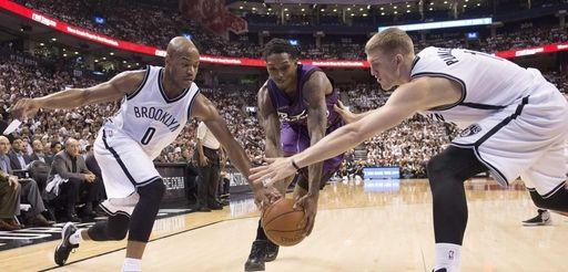 The Toronto Raptors' Lou Williams, center, wins a