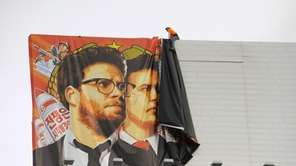 Workers remove a poster-banner for 'The Interview' from