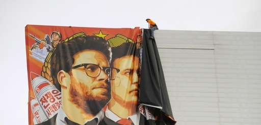 "Workers remove a poster banner for ""The Interview"""