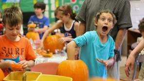 Julia Knobloch, 9, reacts as she guts a