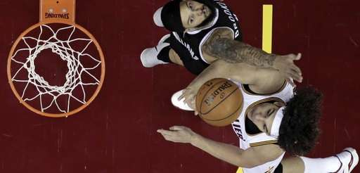 Cleveland Cavaliers' Anderson Varejao, bottom, from Brazil, drives