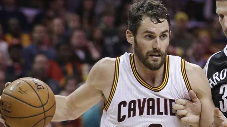 The Cleveland Cavaliers' Kevin Love (0) drives past