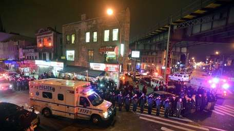 Members of the NYPD salute an ambulance carrying