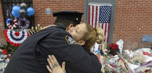 New York City Police officers hug at a