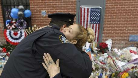 NYPD officers hug at a makeshift memorial for