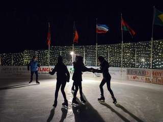 Young skaters circle the ice rink during a