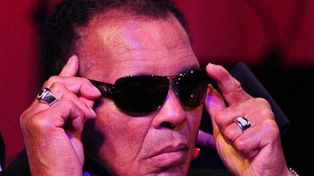 Boxing legend Muhammad Ali adjusts his glasses on
