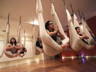 Anti-gravity yoga participants assume yoga positions at Emerge