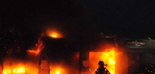 Firefighters battle a fire at the BP gas