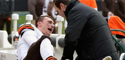 A trainer tends to Johnny Manziel #2 of