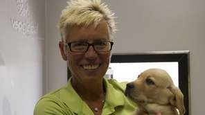 Marchon volunteer Patty Weber holds a Labrador retriever