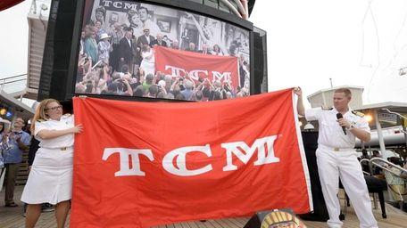 Disney Magic crew members unfurl the banner as