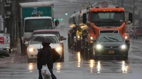 A woman shields herself from the rain with