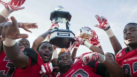 Western Kentucky football players hold up the trophy
