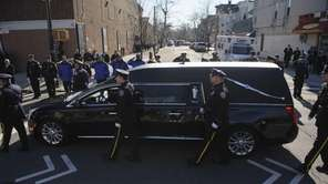 A hearse carrying the casket of NYPD Officer