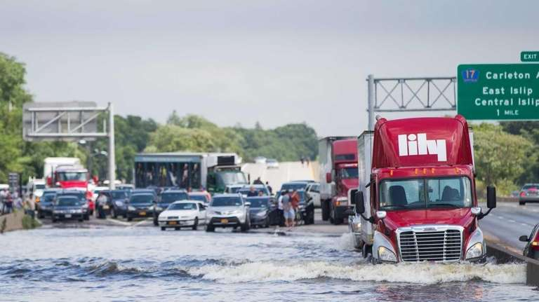 A trailer truck drives through flooded Sunrise Highway
