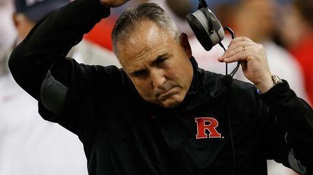 Head coach Kyle Flood adjusts his headset while