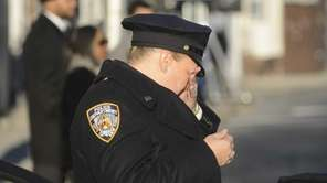 An NYPD officer becomes emotional as she stands