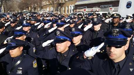 Officers stand at attention during the funeral procession