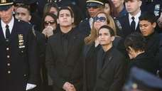 Officer Rafael Ramos' wife Maritza is flanked by