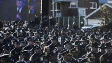 Police officers outside the church turn their backs