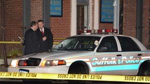 Detectives investigate the scene where a Suffolk County