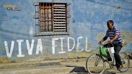 A Cuban rides his bicycle by graffiti hailing