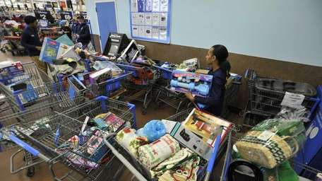 Walmart workers sort through carts of returned items