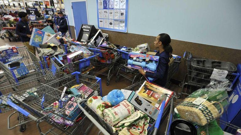 Walmart workers sort through carts of returned items