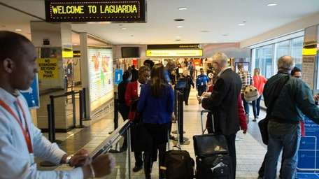 Travelers enter a security checkpoint at LaGuardia Airport