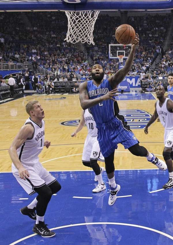 Orlando Magic's Kyle O'Quinn, center, shoots as he