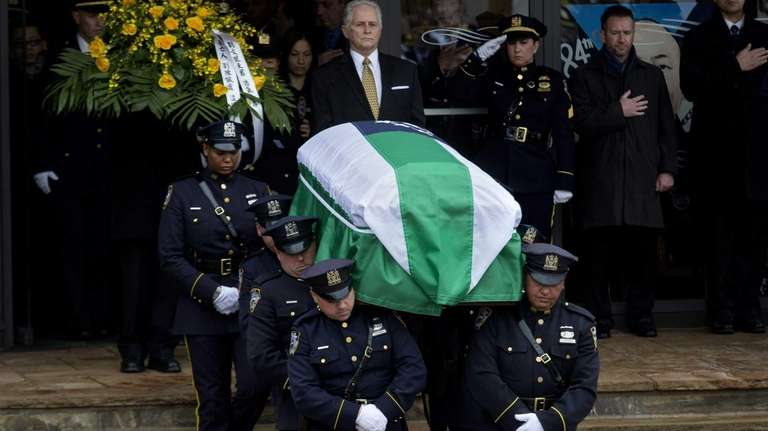 NYPD officers carry the coffin of Det. Wenjian