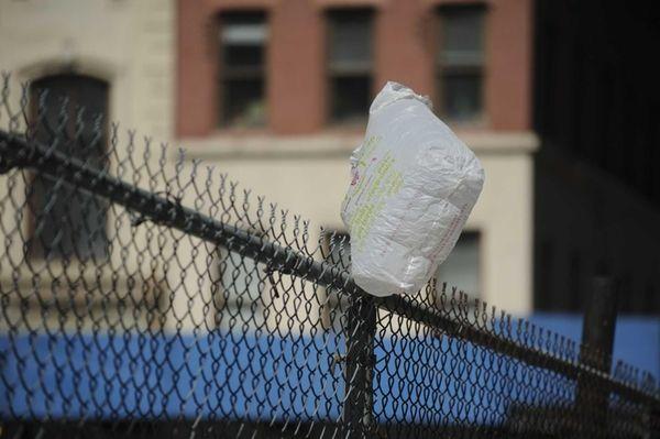 A plastic bag stuck on a fence on