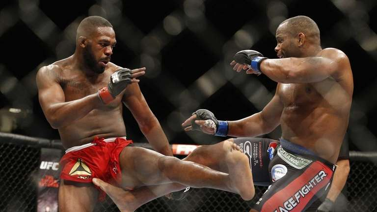 Daniel Cormier, right, kicks Jon Jones during their