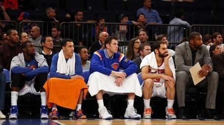 The New York Knicks bench looks on late