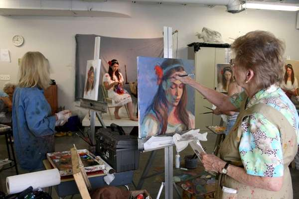 Artists work on their paintings of a model