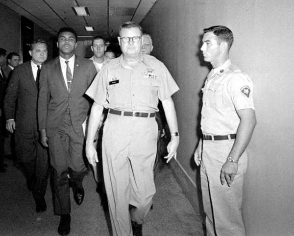 Heavyweight champion Muhammad Ali is pictured being escorted
