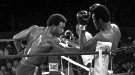 George Foreman, left, throws a punch at Muhammad